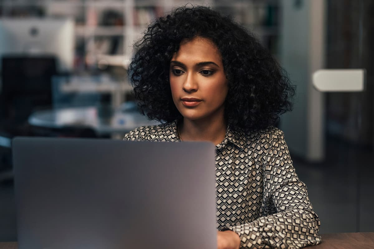 Beautiful young woman working on her laptop pc at her office