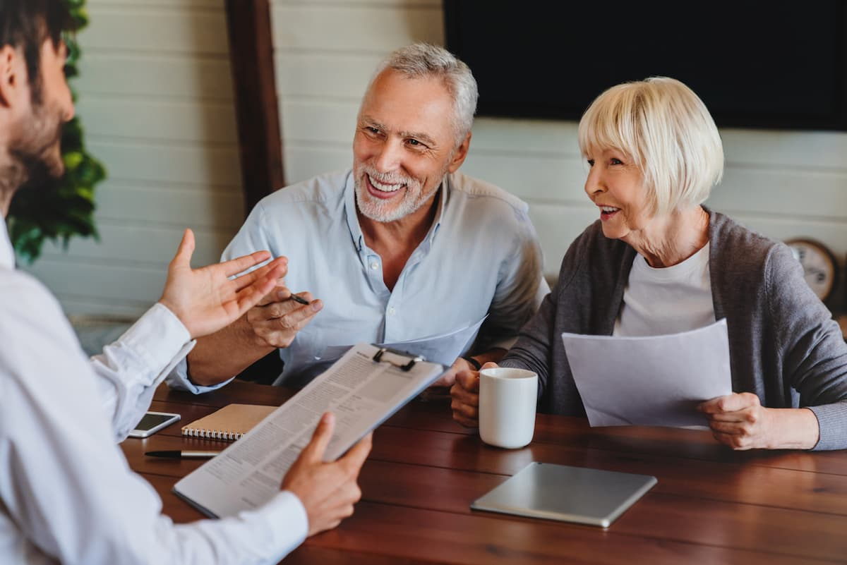 Happy aged couple consulting with insurance agent at home