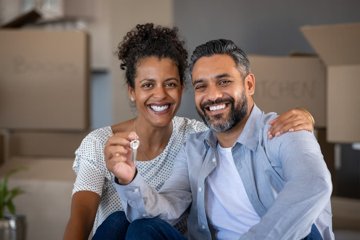 Middle aged multiethnic couple embracing and holding house keys with carboard boxes behind them