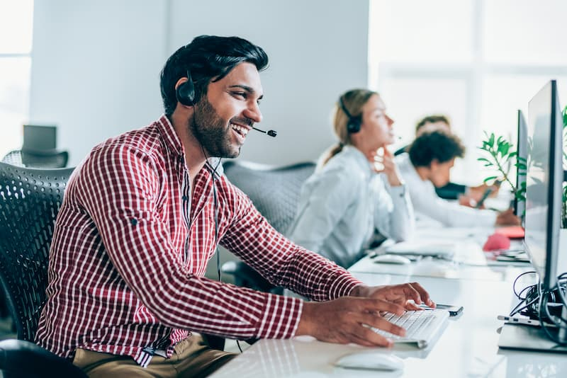 Smiling handsome ethnicity businessman working in call center.
